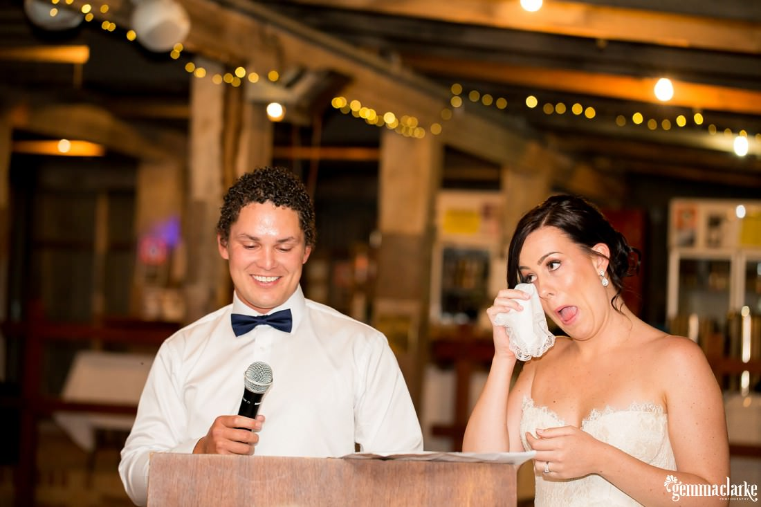A bride wipes a tear from her eye as a groom delivers a speech