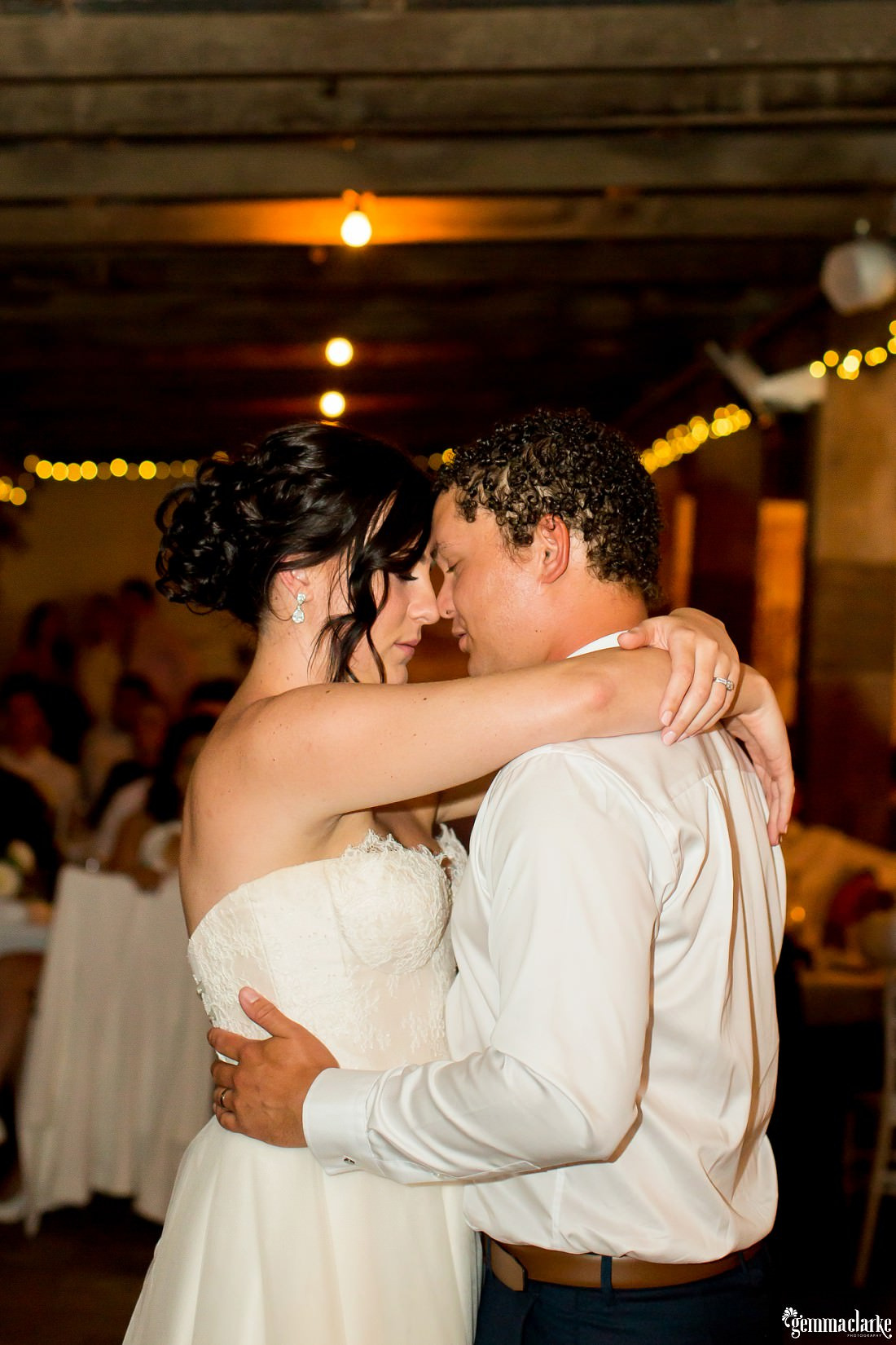 A bride and groom sharing an intimate moment during their first dance at their wedding reception