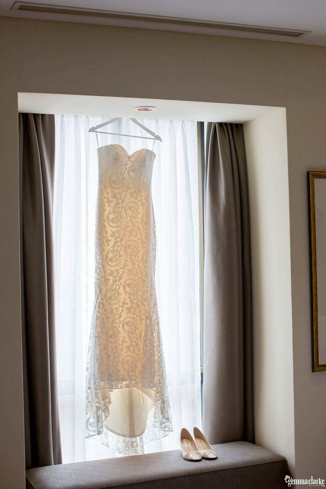 A lovely detailed white bridal gown on a hanger in a window with bridal shoes below