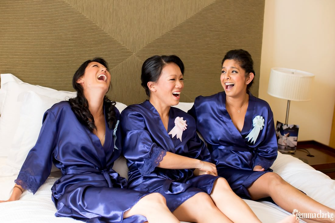 A bride and her bridesmaid in purple robes laugh while sitting on a bed