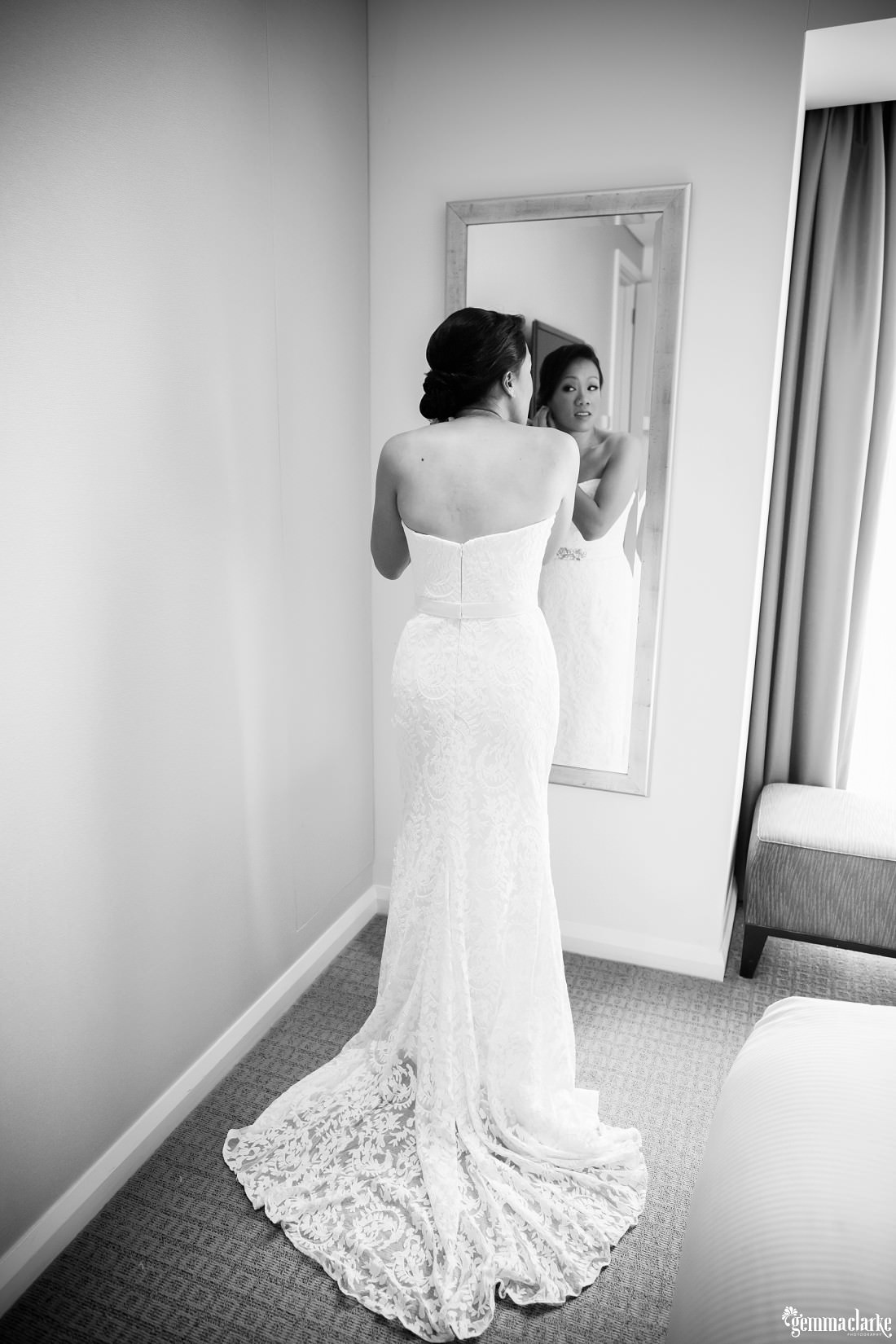 A bride in a white bridal gown puts on her earrings in front of a mirror
