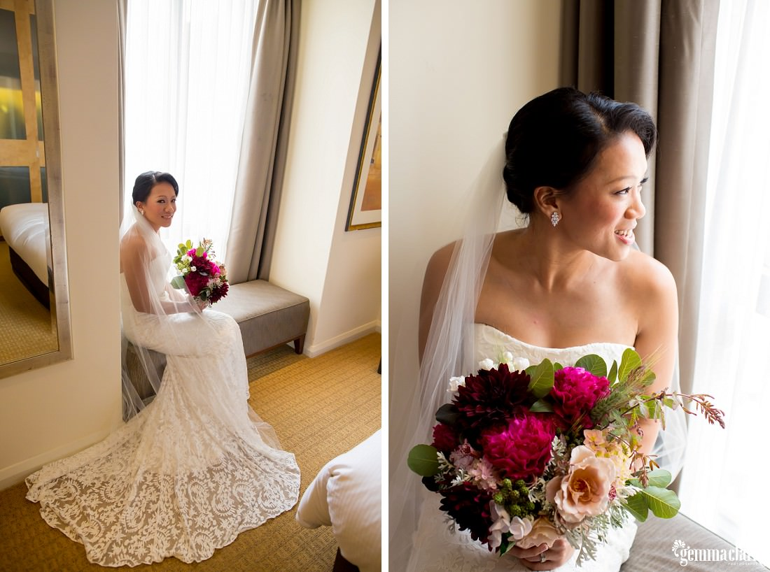 A bride smiles and poses on a bench seat near a window while holding her bouquet