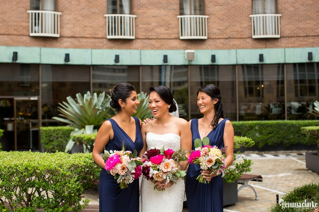 A bride and her bridesmaids smile and pose together in a hotel courtyard