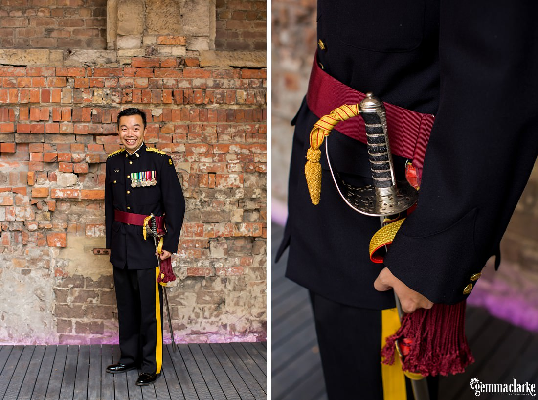 A smiling groom posing and showing his ceremonial army uniform with medals and sword