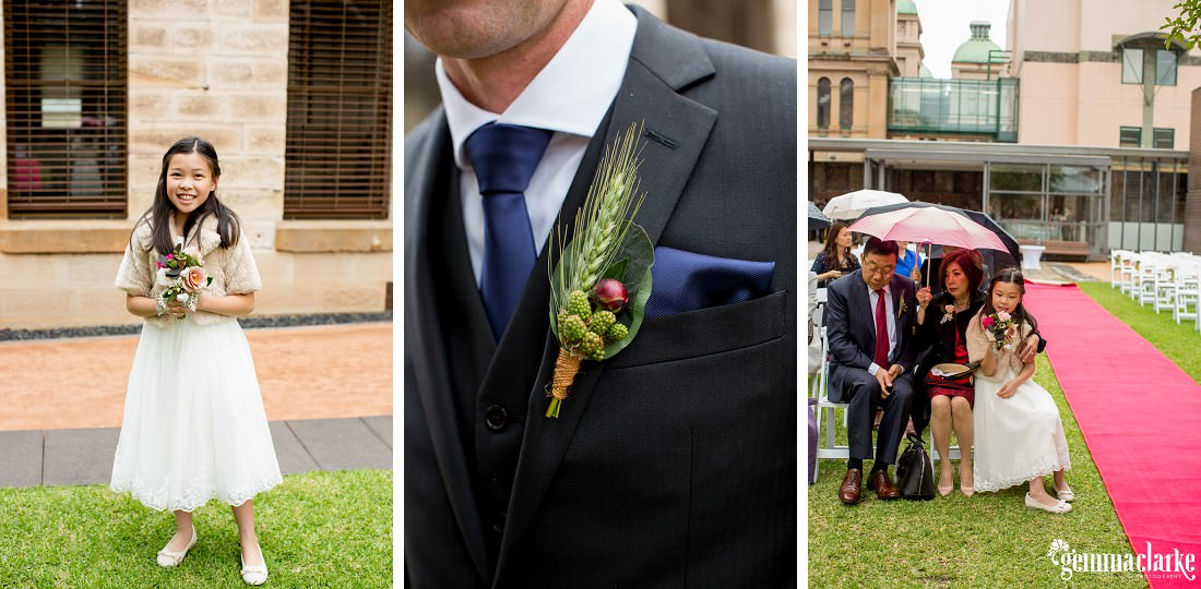 A closeup of a groomsman's floral buttonhole and pocket square, a young girl in a white dress, and wedding guests huddling under umbrellas