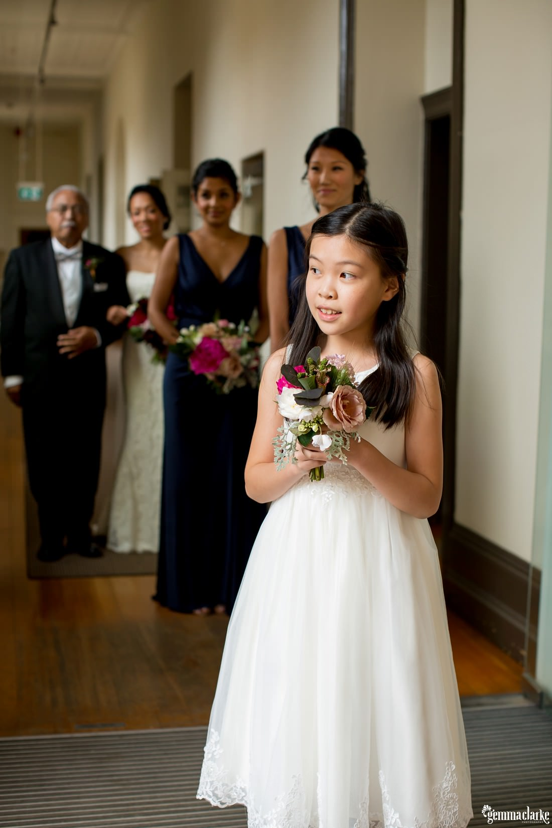 A flower girl peaks out to the ceremony as the bridesmaids and the bride and her father wait behind