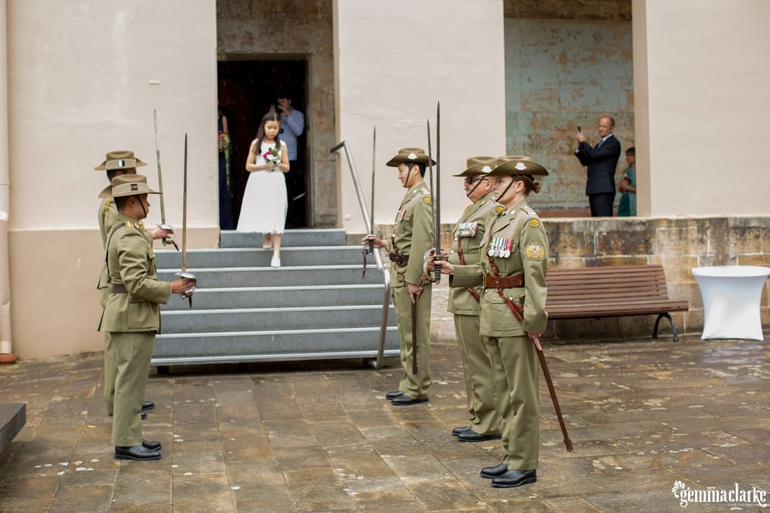 A flower girl walks down steps as army personnel with ceremonial swords stand either side
