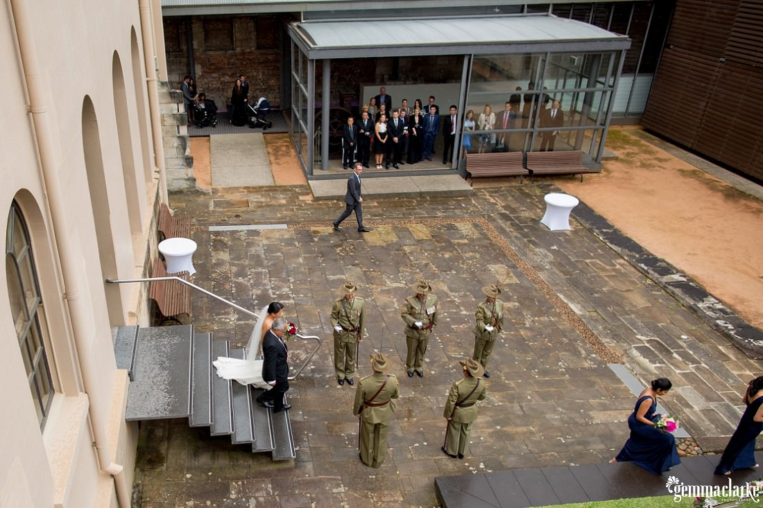 An overhead shot of a bride being walked to her ceremony by her father between army personnel with ceremonial swords