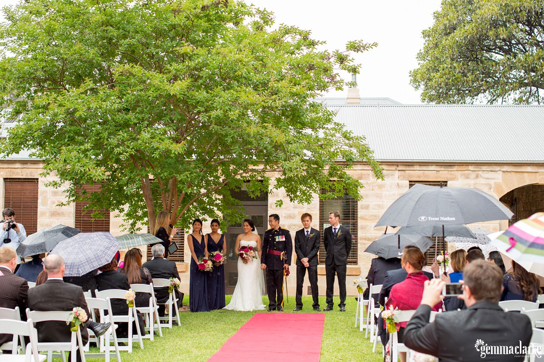 A bride and groom and their bridal party stand under a tree at the end of the aisle as their wedding guests sit underneath umbrellas