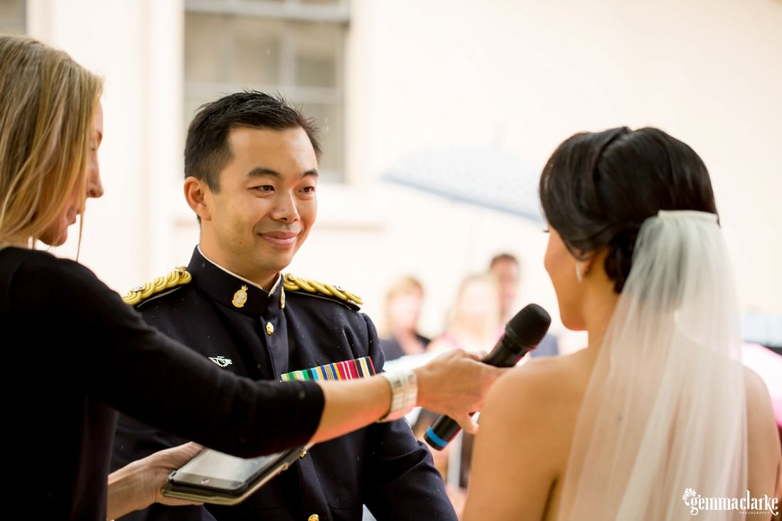 A bride speaks into a microphone held by the celebrant as her smiling groom looks at her