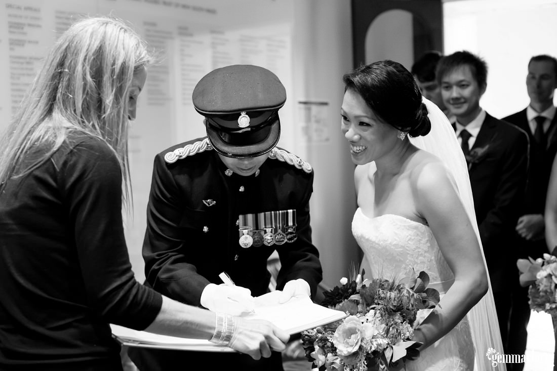 A bride and groom signing their wedding papers