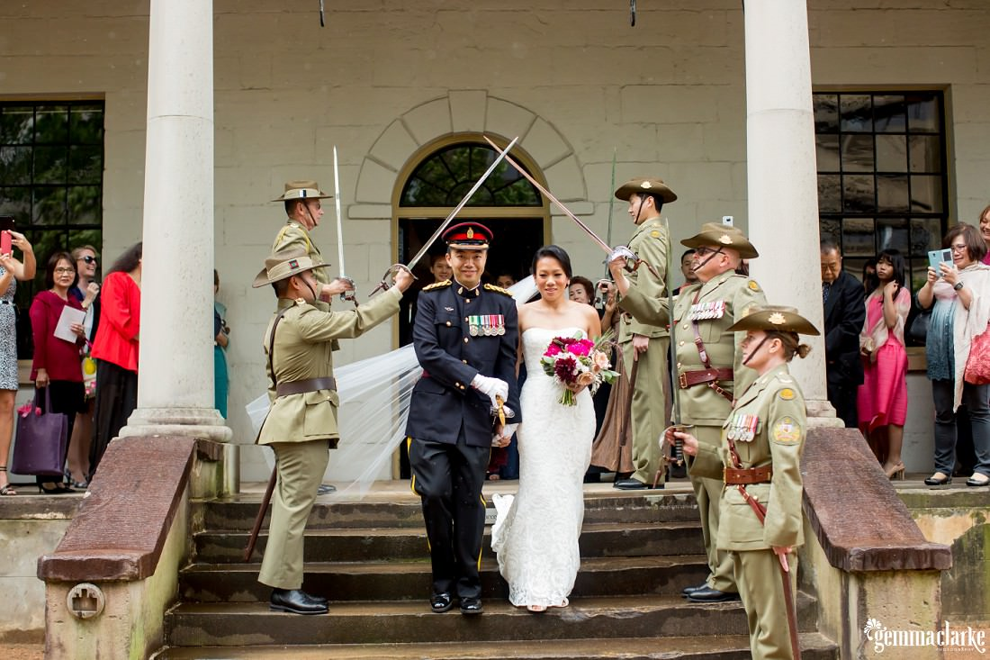 A bride and groom walk down steps underneath ceremonial swords held by uniformed army personnel