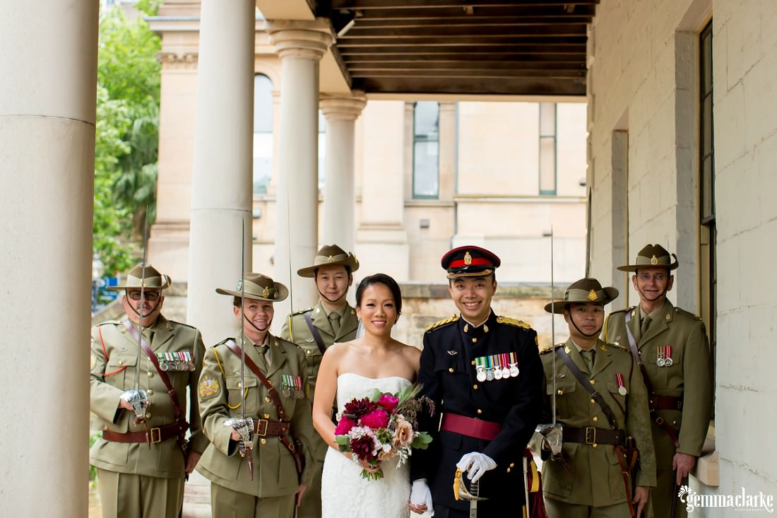 A smiling bride and groom posing with army personnel