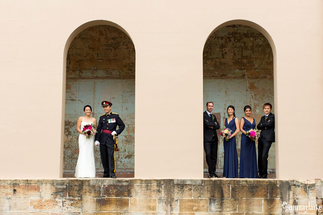 A bride and groom posing with their wedding party beneath two archways