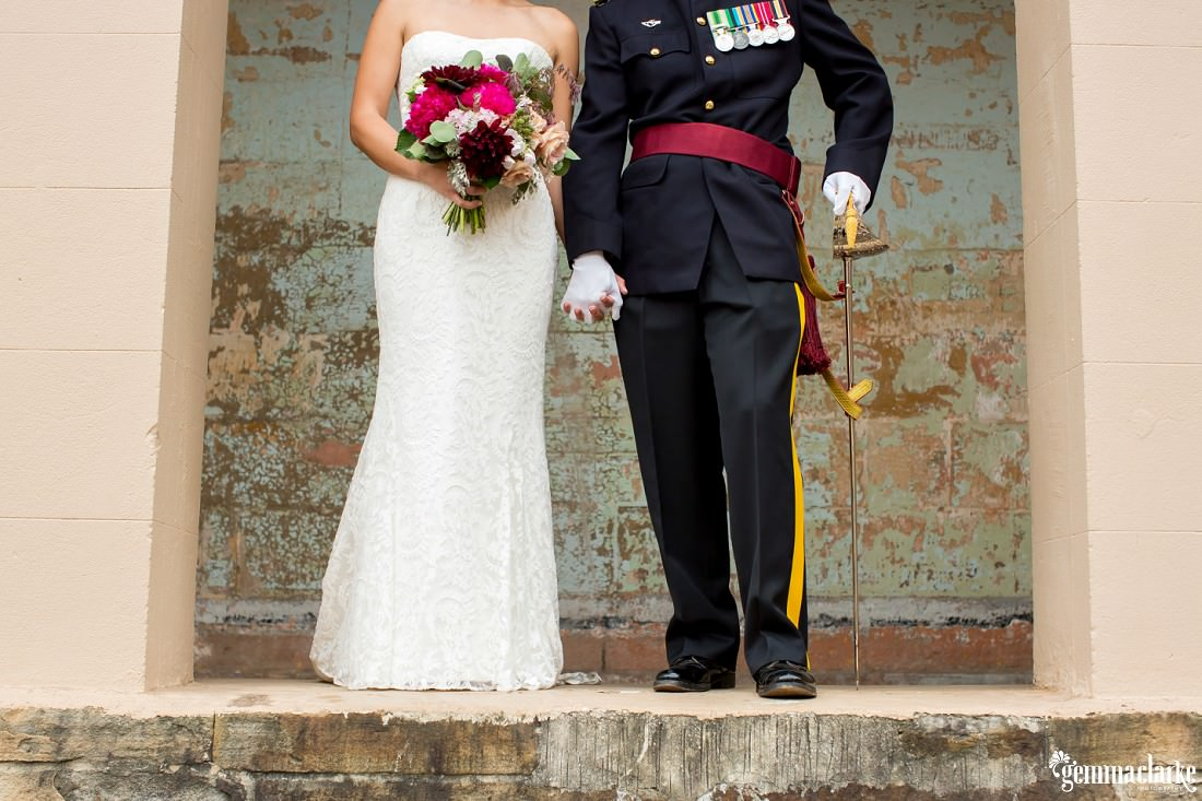 A low shot showing off the bride and groom's attire as they hold hands while standing in an archway