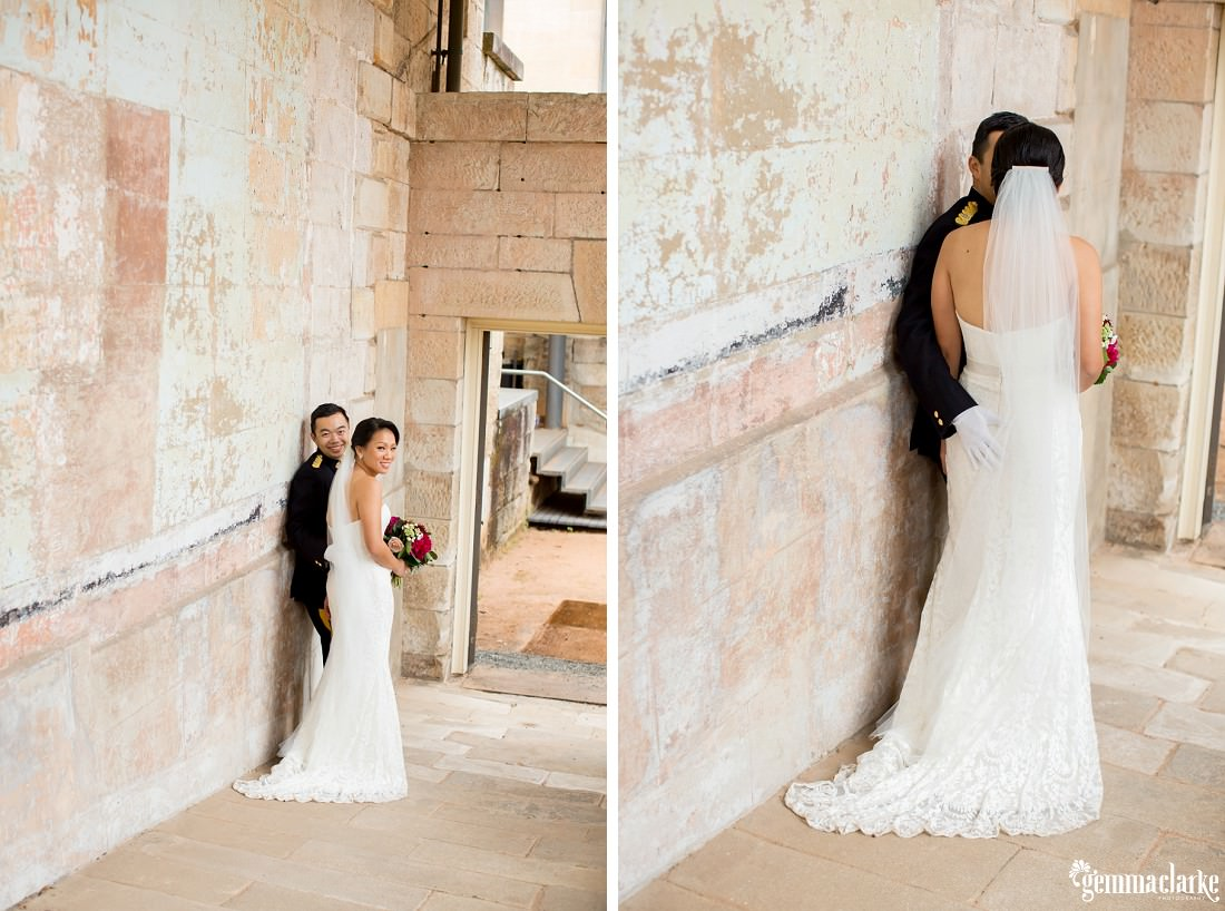 A bride and groom look back over their shoulders from the bottom of a ramp