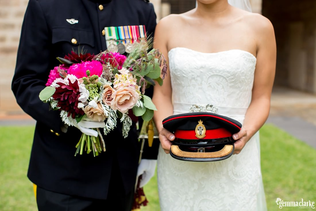 A bride holds her groom's hat, and the groom holds his bride's bouquet