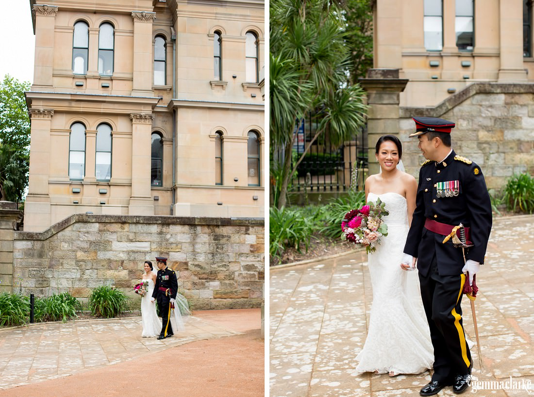 A bride and groom holding hands and walking together past vintage looking building