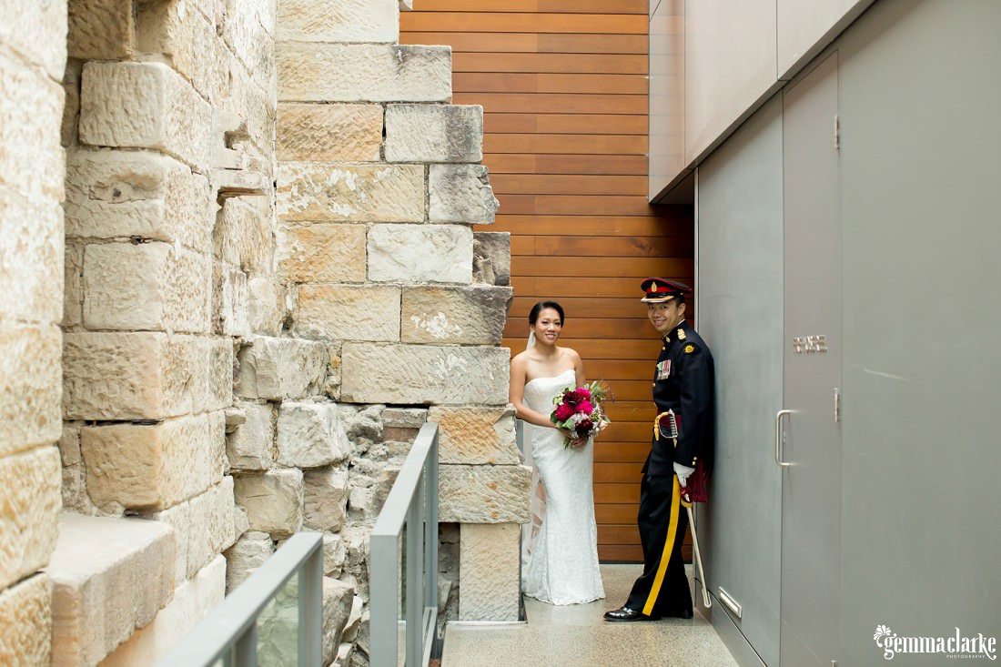 A groom leans against a wall and his bride leans against a stone wall