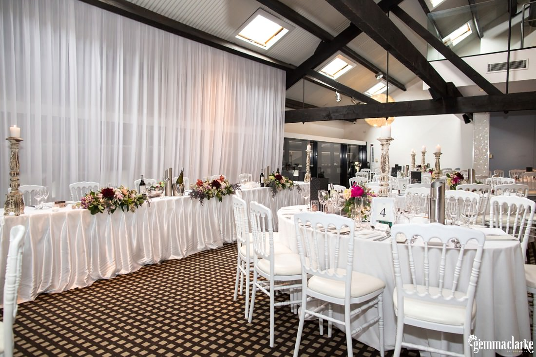 White and floral decorated tables and chairs at a wedding reception