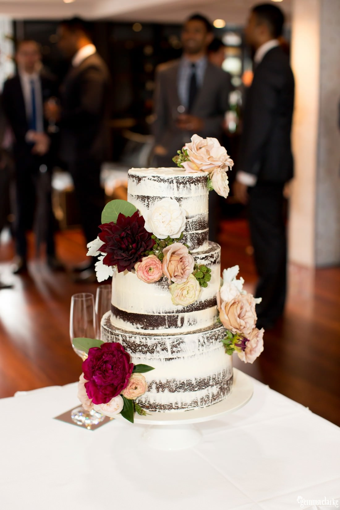 A three tiered naked cake decorated with flowers