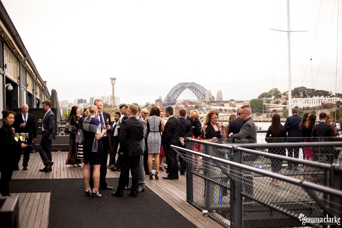 Wedding guests mingling outside of a reception venue with the Sydney Harbour Bridge in the background