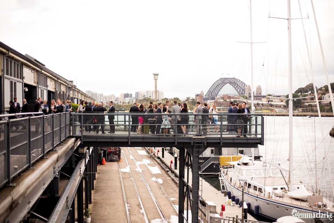Wedding guests mingling outside of a reception venue with boats and the Sydney Harbour Bridge in the background