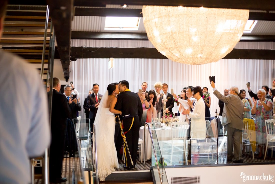 Wedding guests take photos as the bride and groom share a kiss upon entering their reception