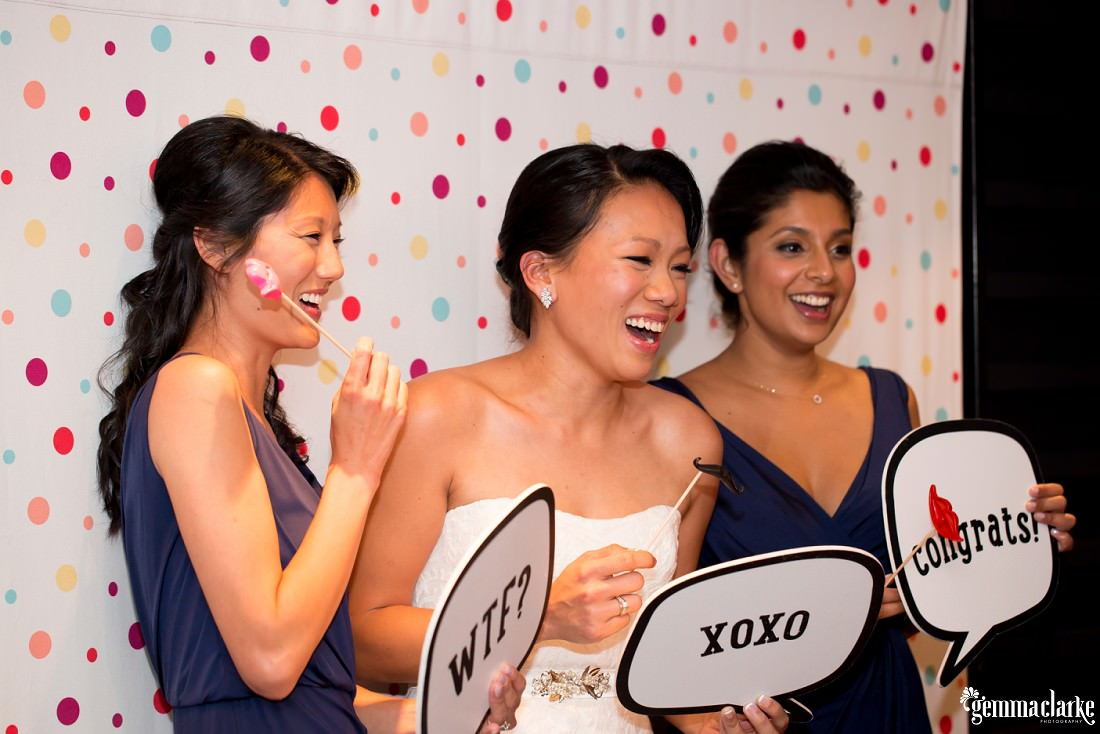 A bride and her bridesmaids smiling and holding props in a photobooth
