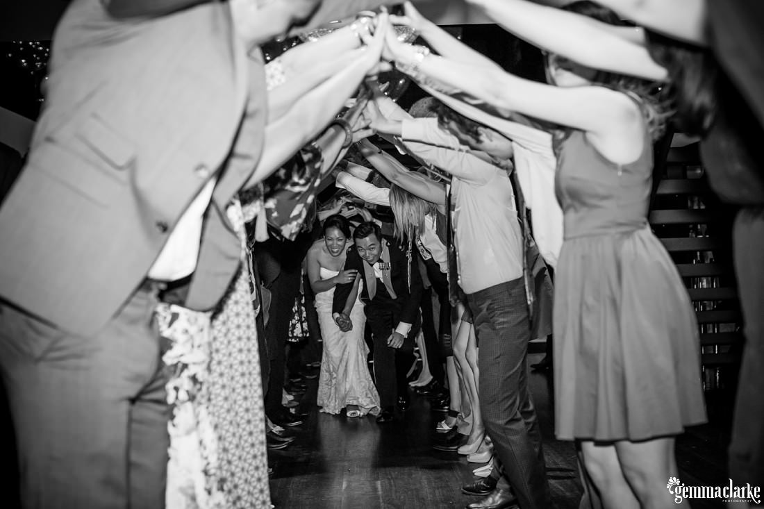 A smiling bride and groom crouch to navigate a farewell arch provided by their wedding guests