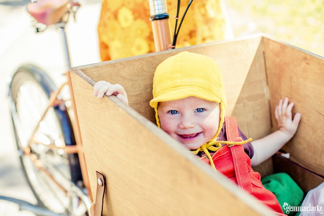 A smiling baby sitting in a wooden box attached to the front of a bicycle