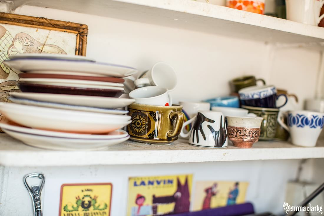 Various dishes and mugs on a shelf in a cafe