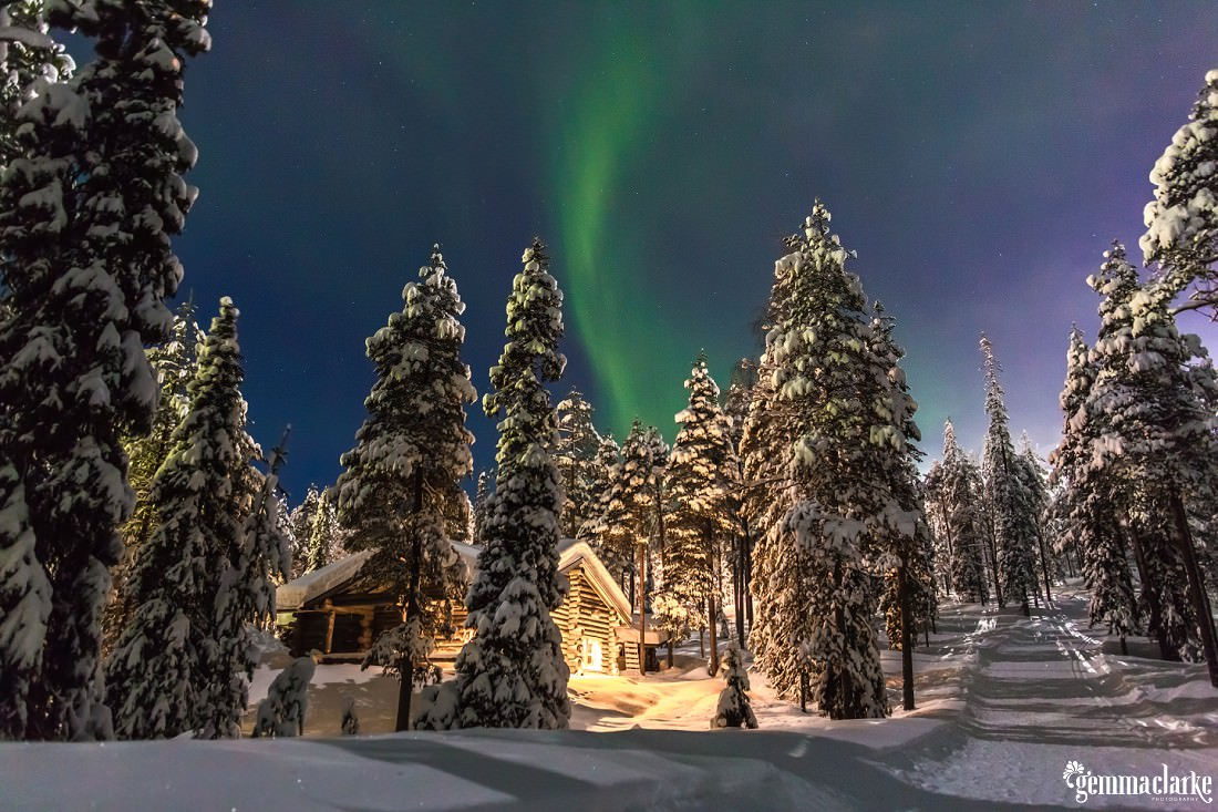 Aurora Borealis over a cabin in a snow covered forest