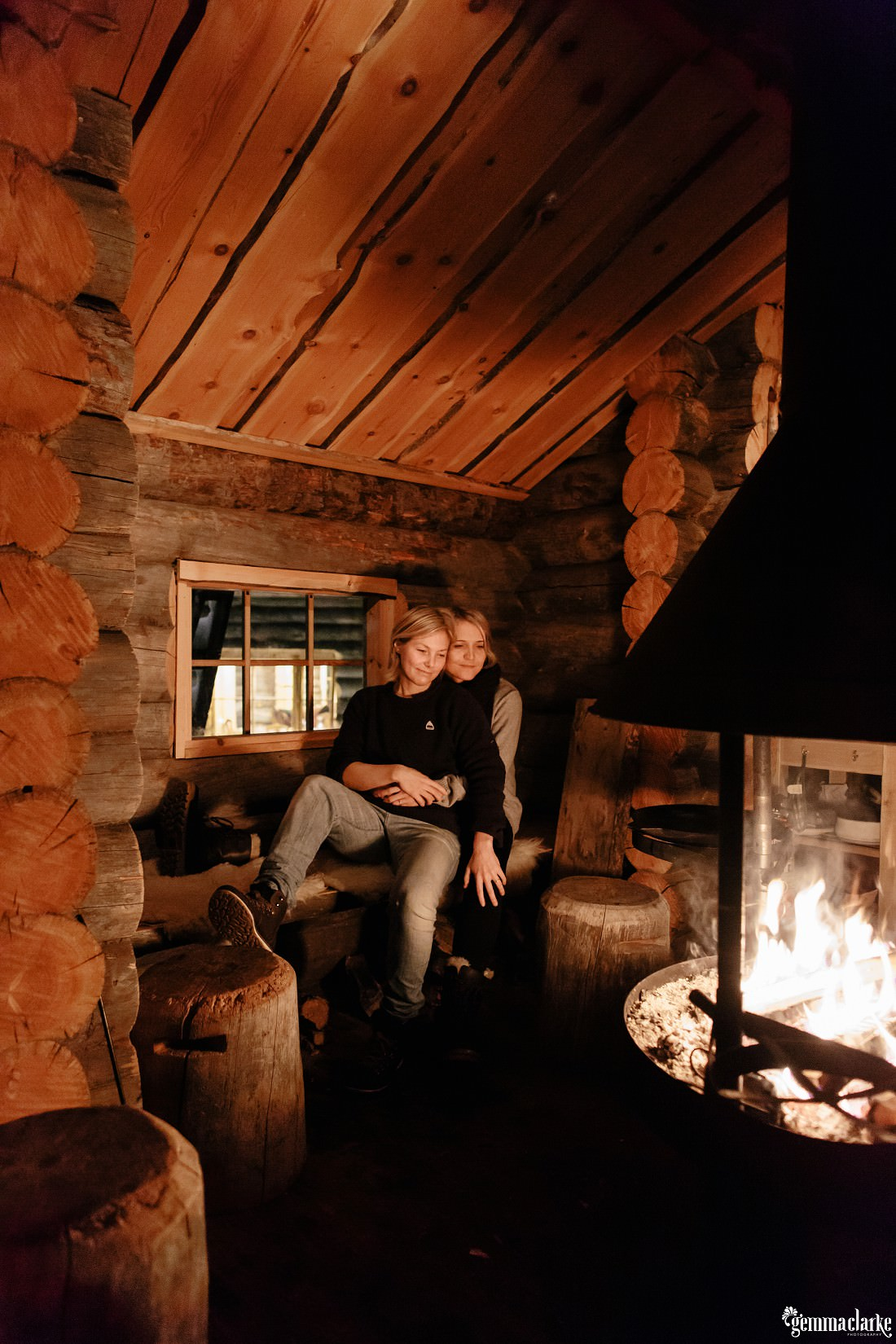 A couple embrace on a bench in front of a fireplace in a wood cabin