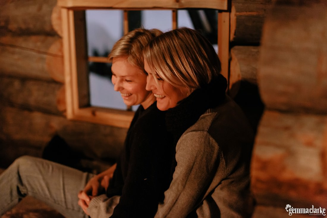 A smiling couple sitting together in a wood cabin