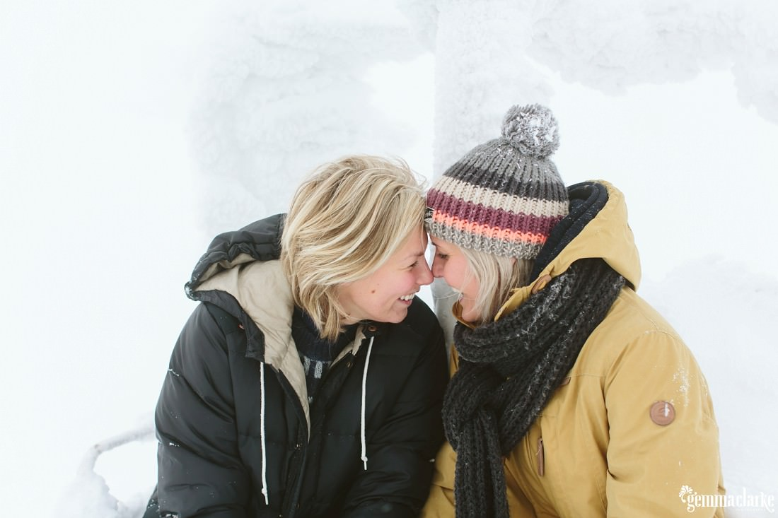 A smiling couple sharing eskimo kisses while sitting on a snow covered ski lift