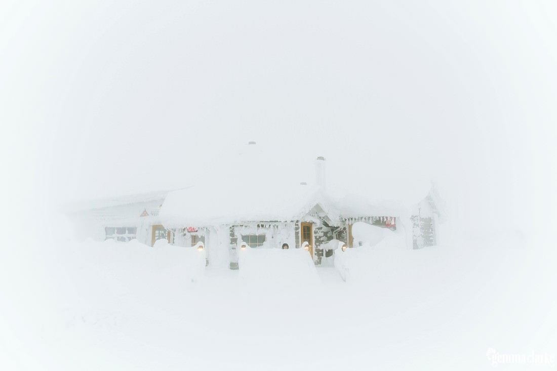 A cabin covered in and surrounded by very thick snow