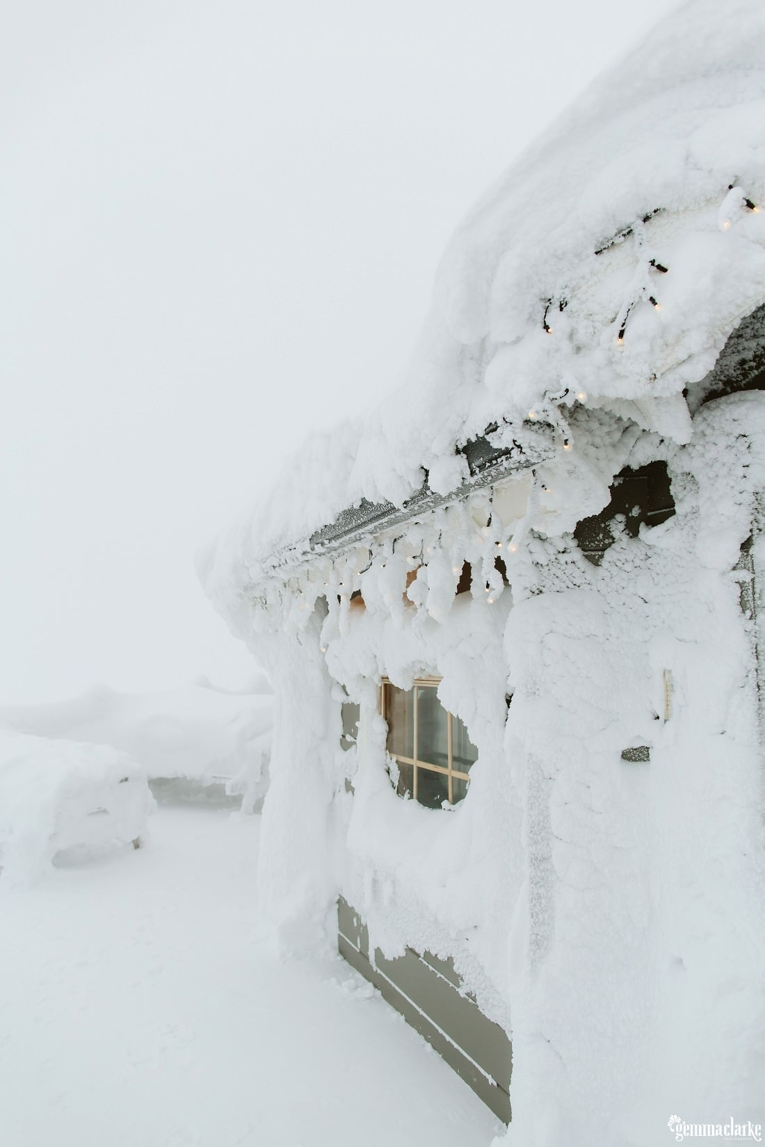 Very thick snow hanging from the roof of a cabin