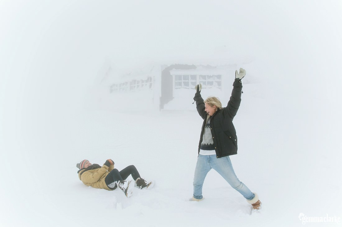 A couple playing in very heavy snow