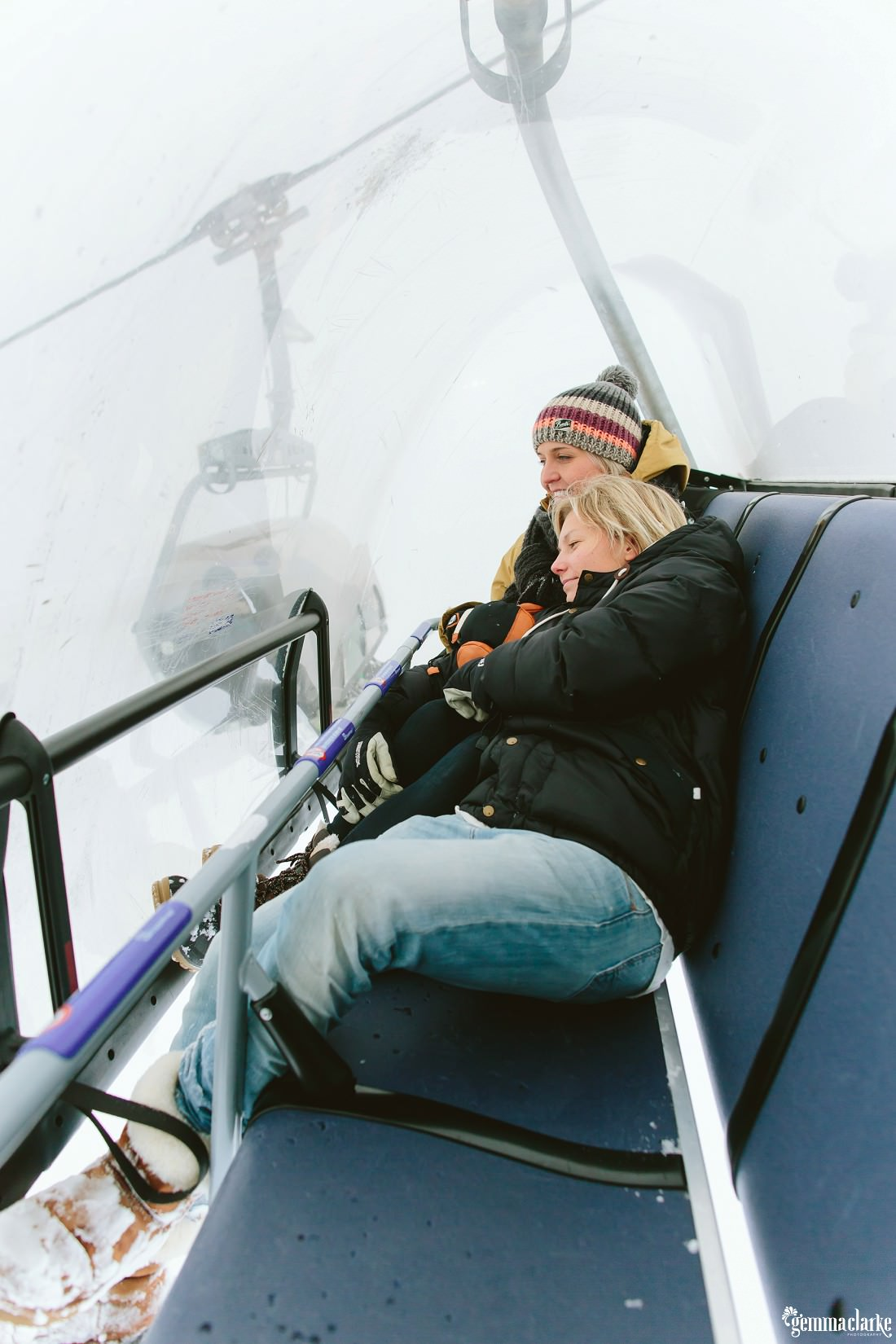A smiling couple sit close together on a ski lift