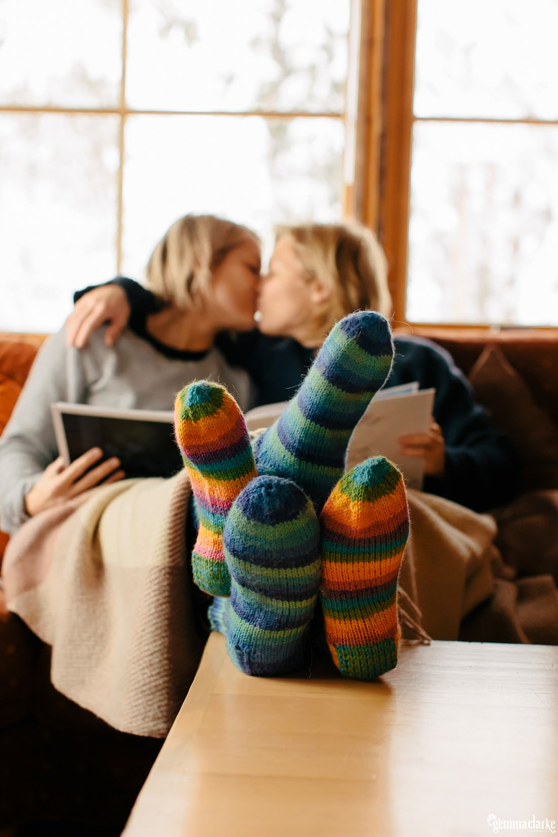 A couple kiss while sitting together in a couch with their feet in colourful stripey socks are entwined on a table