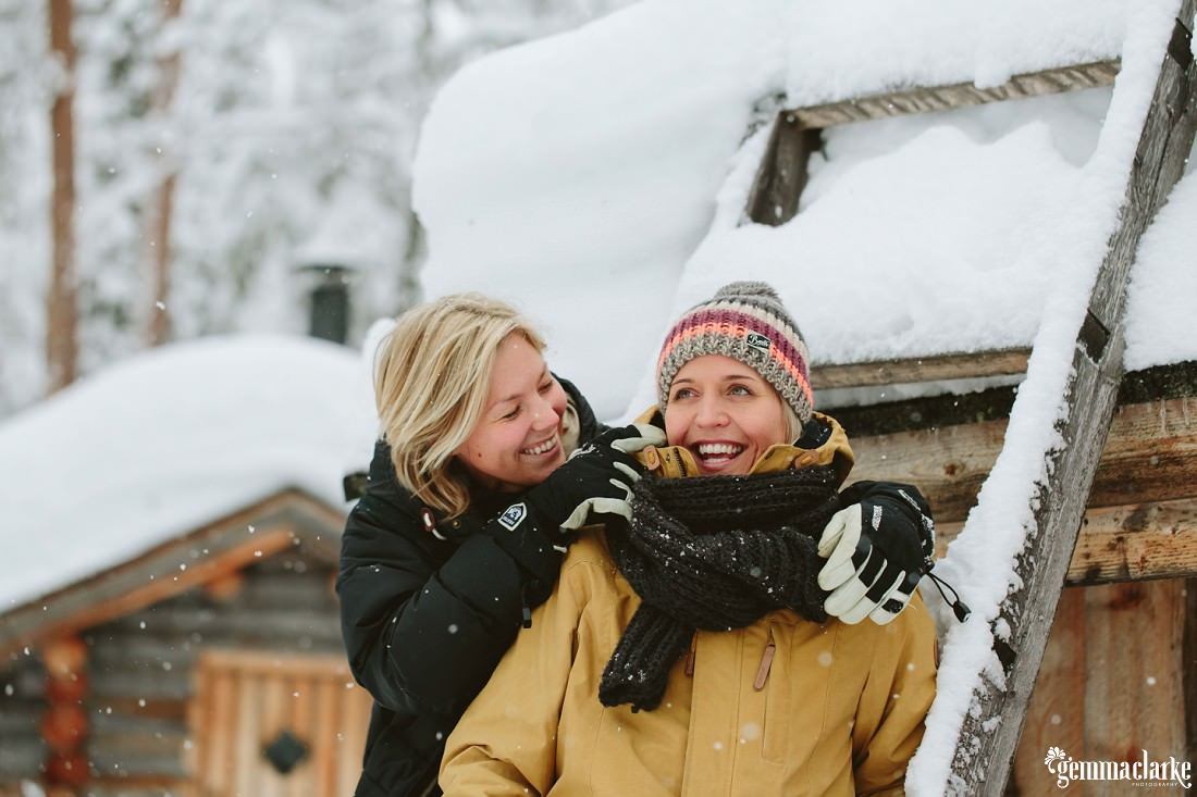 A smiling couple in front of a snow covered ladder and cabin