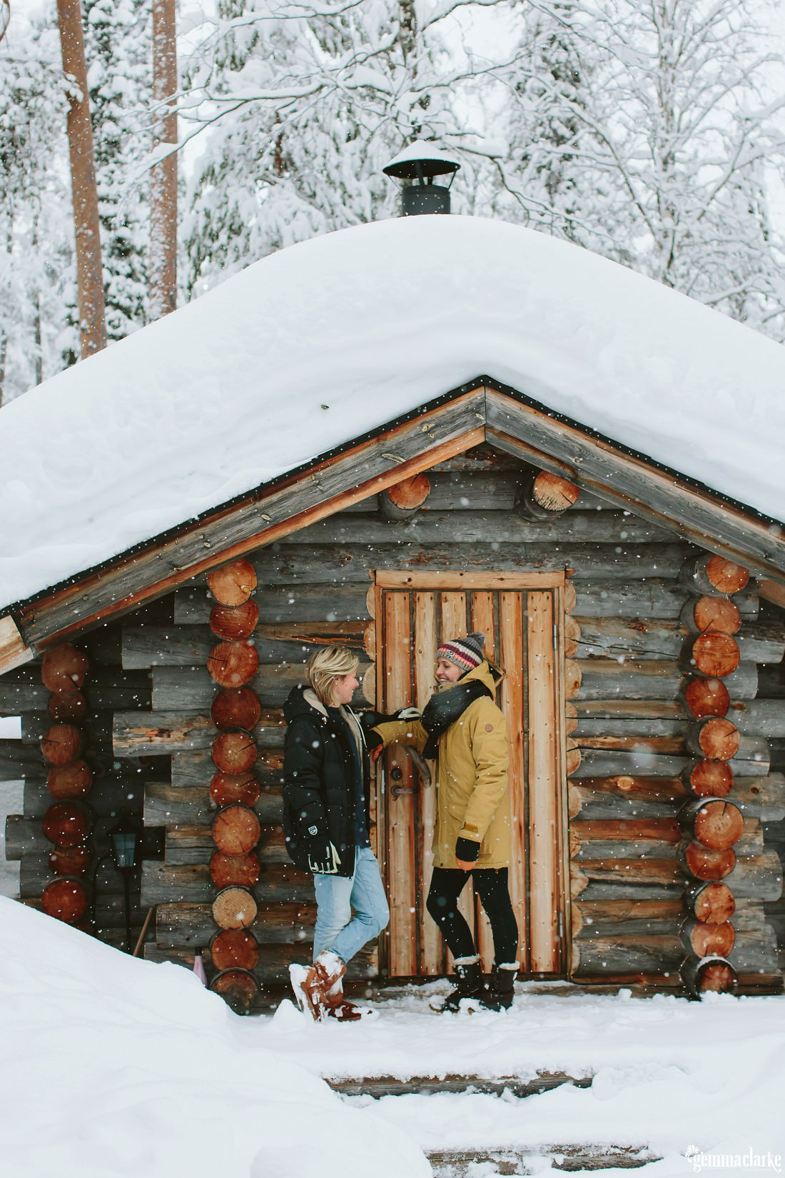 A couple smile at each other while standing in front of a snow covered wood cabin