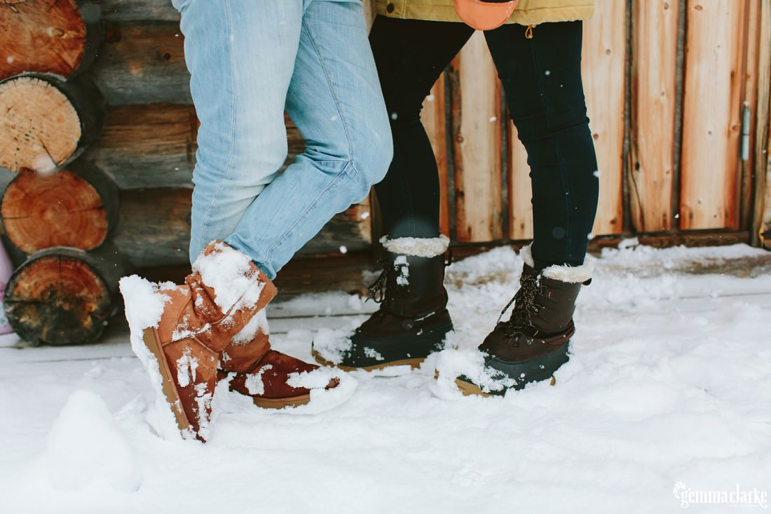 A closeup of a couple's snow covered snows as they stand close in front of a wooden cabin