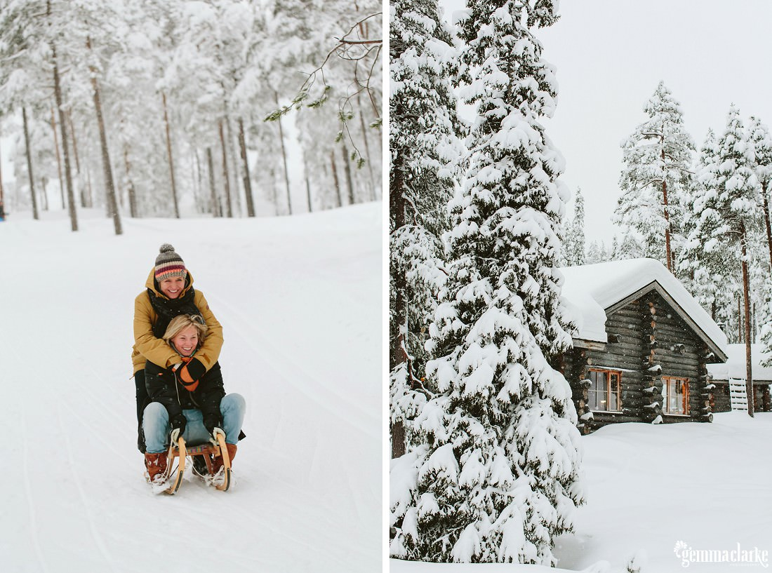 A smiling couple playing on a sled in the snow, and a cabin in a snow covered forest