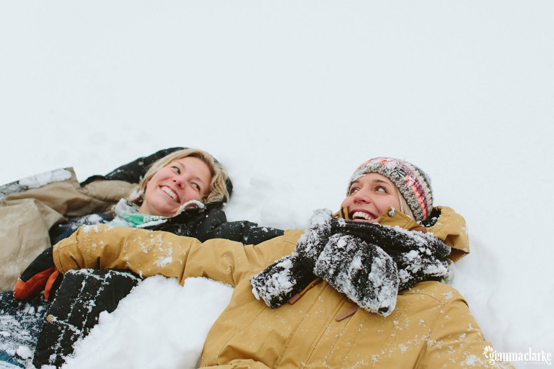 A smiling couple lay next to each other in the snow