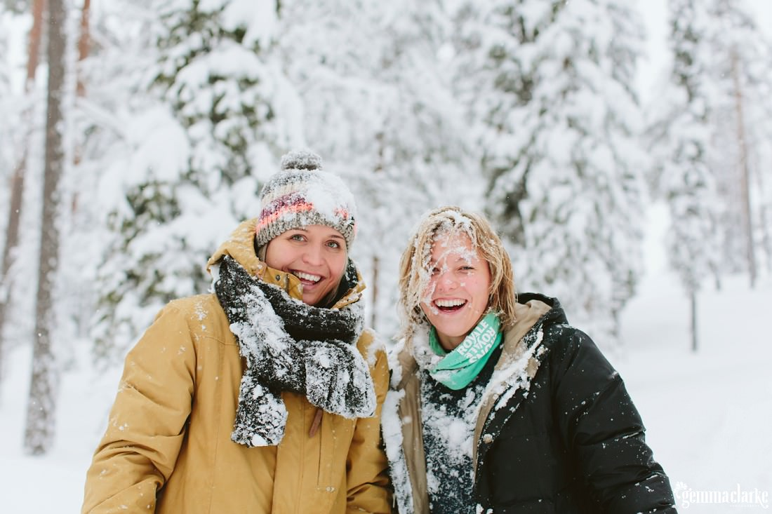 A smiling couple covered in snow after a snowball fight