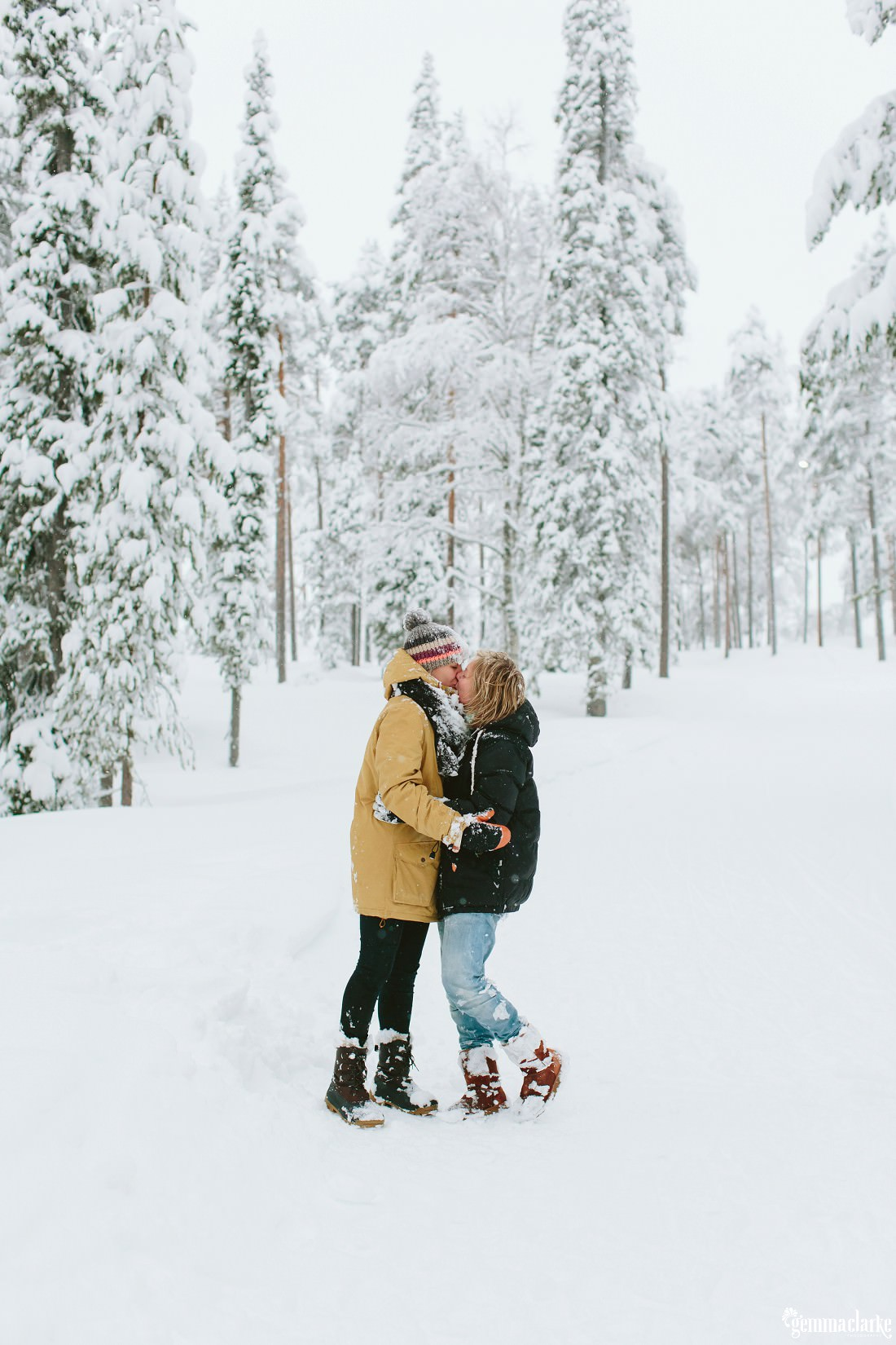 A couple kissing in a snow covered forest