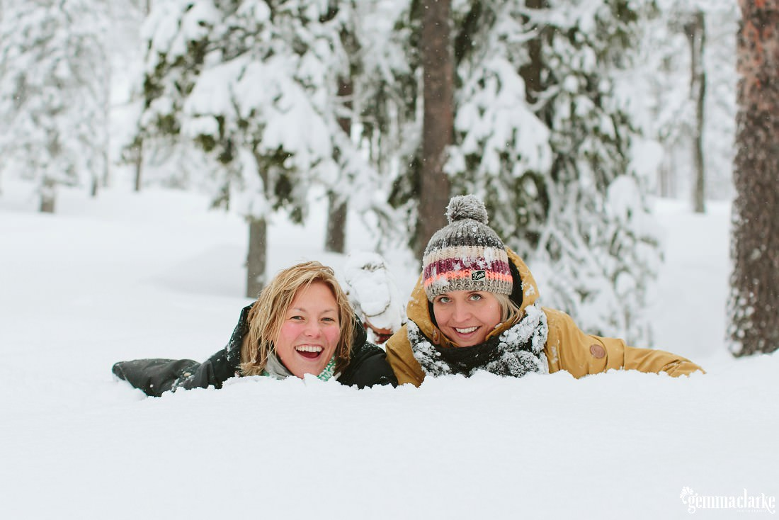 A smiling couple laying in the snow