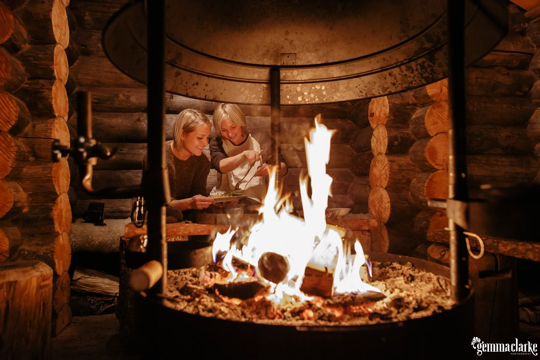 A smiling couple serving salmon in front of an open fire